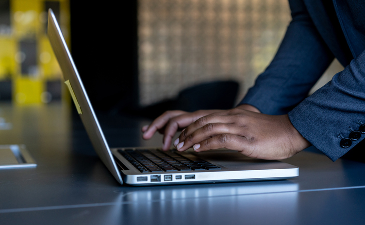 Unrecognizable black woman at the office typing on laptop